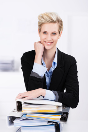 Wissensmanagement: Junge Frau lächelt wissend auf Aktenordner gestützt