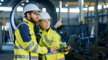 Produktion: Mann und Frau mit Laptop in einer Produktionshalle